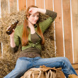 Provocative young cowgirl drink beer in barn - 图库照片