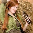 Provocative young cowgirl drink beer in barn — Stock Photo