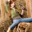 Provocative young cowgirl drink beer in barn — Stock Photo #5757177