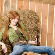 Stock Photo: Provocative young cowgirl drink beer in barn