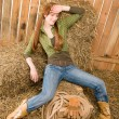Stock Photo: Provocative position young cowgirl on hay