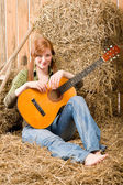 Young country woman sitting on hay with guitar — Stock Photo