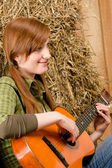 Young country woman playing guitar in barn — Stock Photo