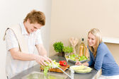 Lunch happy couple cook salad in kitchen — Stock Photo