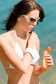 Summer young woman with suncream in bikini — Stock Photo