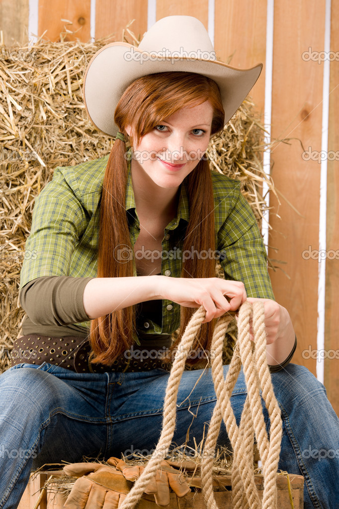 Young cowgirl western country style sitting in barn — Stock Photo #5757165