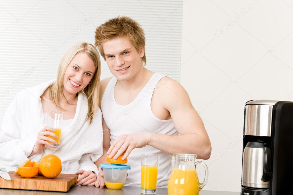 Breakfast happy young couple make orange juice in morning kitchen — Stock Photo #5757322