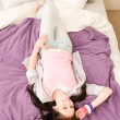 Young happy student relax lying on bed — Stock Photo #5879393
