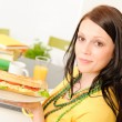Young student girl eat sandwich in kitchen — Stock Photo
