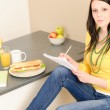 Young happy student have sandwich in kitchen — Stock Photo