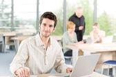 Portret van jonge zakenman met team in de rug — Stockfoto