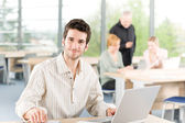 Portrait of young businessman with team in back — Stock Photo