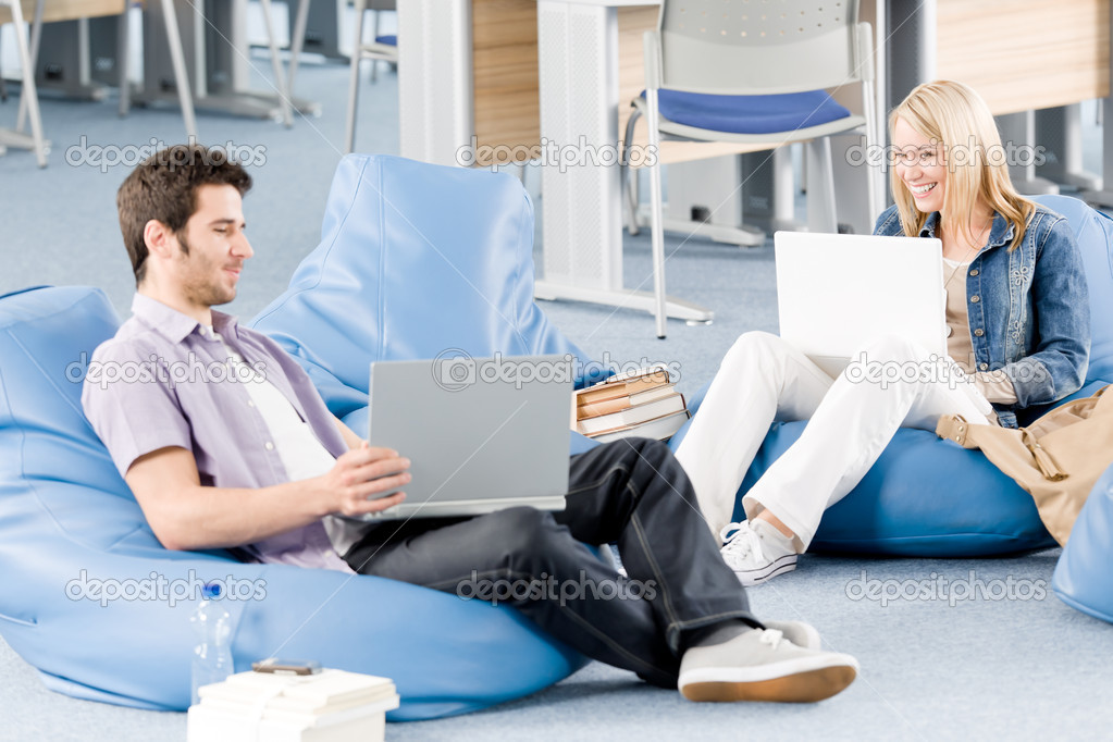 Young students at high-school relaxing pointing at laptop  Stock Photo #5879481