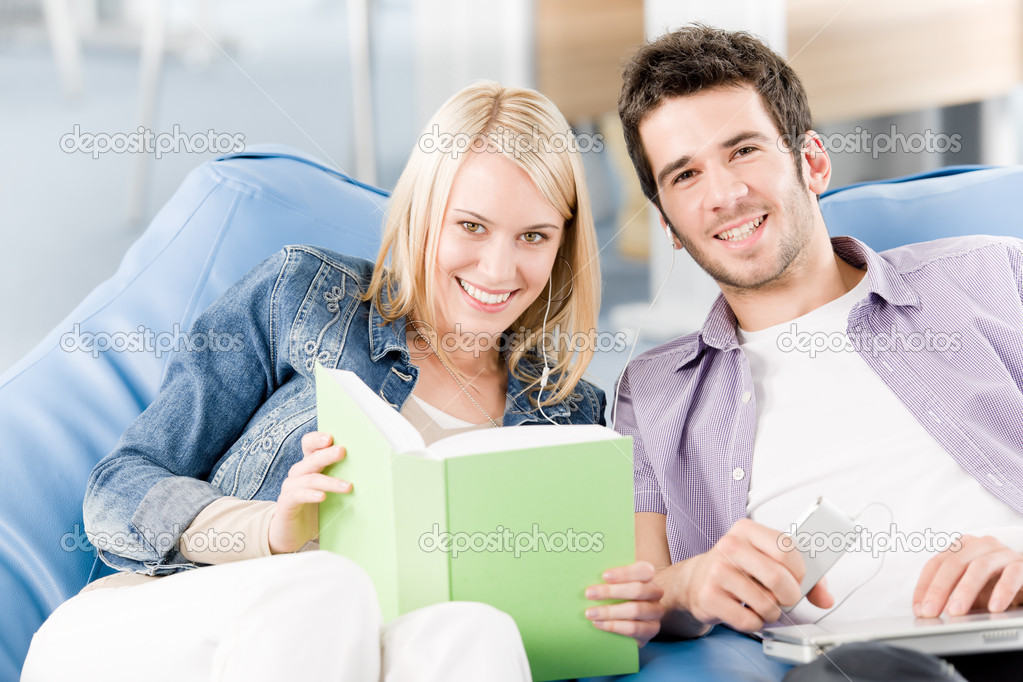 Smiling young high-school students reading book listen music — Stock Photo #5879541