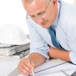 Professional architect with blueprint behind table — Stock Photo