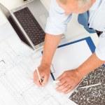 Senior man work on blueprints construction plans — Stock Photo