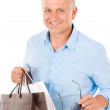 Mature smilling man hold shopping bags - Lizenzfreies Foto