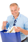 Mature smilling man hold shopping bags — Stock Photo