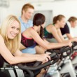 Young fitness bike spinning with instructor - Stok fotoğraf