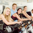 Young fitness bike spinning with instructor — Stock Photo #5939327