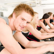 Stock Photo: Fitness young man on gym bike spinning