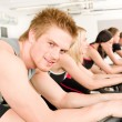 Fitness young man on gym bike spinning — ストック写真