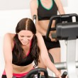 Fitness young girl on gym bike — Stock fotografie