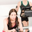 Foto Stock: Fitness young girl on gym bike