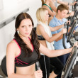 图库照片: Fitness young group on elliptical cross trainer