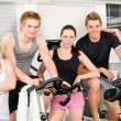 Foto Stock: Fitness young group at gym bicycle
