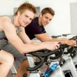Fitness young man on gym bike spinning — Stock Photo