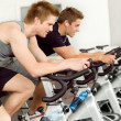 Fitness young man on gym bike spinning — 图库照片