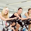 Foto Stock: Fitness young woman on gym bike spinning