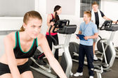 Young fitness woman doing spinning with instructor — Stock Photo