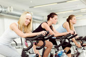Fitness young woman on gym bike spinning — ストック写真