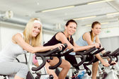 Fitness young woman on gym bike spinning — Photo
