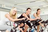 健身年轻的女子在健身房自行车纺 — 图库照片
