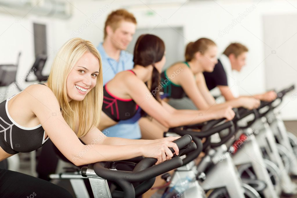Young fitness doing spinning with instructor at gym  Foto Stock #5939326