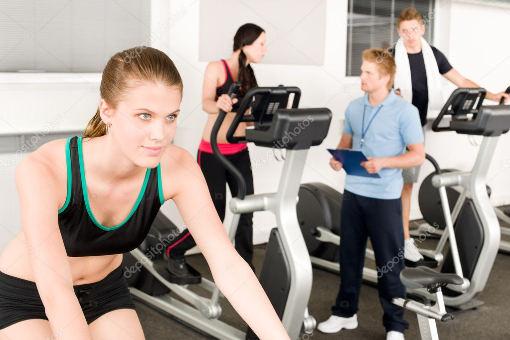 Young fitness woman doing spinning on bicycle with gym instructor — Stock Photo #5939331