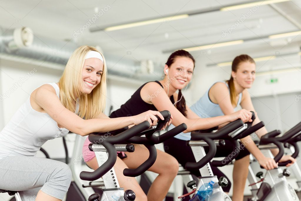 Fitness young woman on gym bike spinning indoor cardio exercise — Stok fotoğraf #5939379