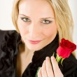 Elegant blond woman hold red rose - Stockfoto