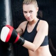 Boxing training woman in black hold punching bag — Stock Photo #6129777