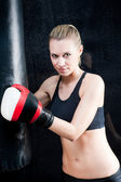 Boxing training woman in black hold punching bag — Stock Photo