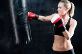 Boxing training woman punching bag in gym — Stock Photo
