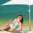 Summer beach woman blue bikini under parasol — Stock Photo #6138188
