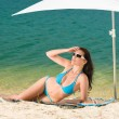 Summer beach woman blue bikini under parasol — Stock Photo