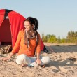 Camping happy woman sitting by campfire on beach - Foto Stock