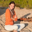 Camping woman relax on beach by campfire — Stock Photo