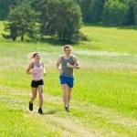 Sportive young couple jogging meadows sunny summer — Stock Photo
