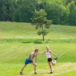 Sportive jogging couple stretching in countryside — Stock Photo
